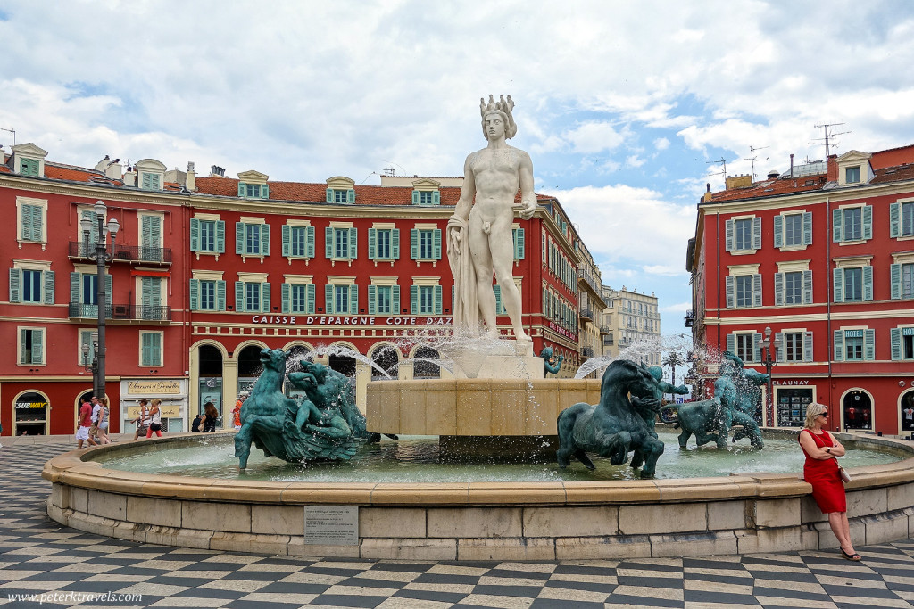 A woman leans against the fountain in Place Massena