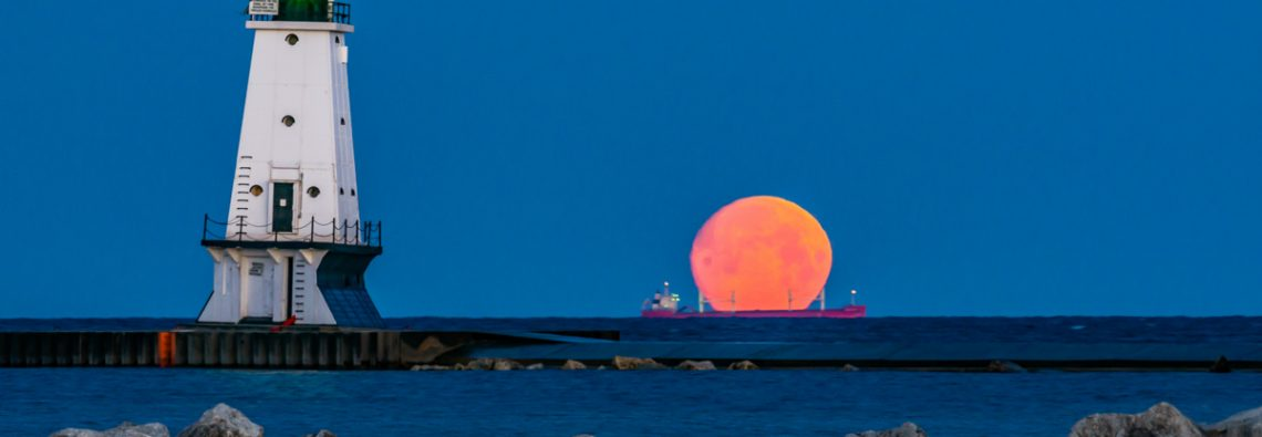 A setting moon and ore carrier, with the Ludington Lighthouse.